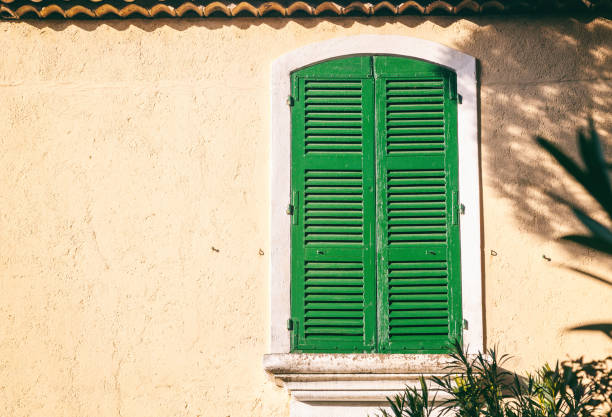 Details of French Provencal architecture, a window with green shutters - foto stock