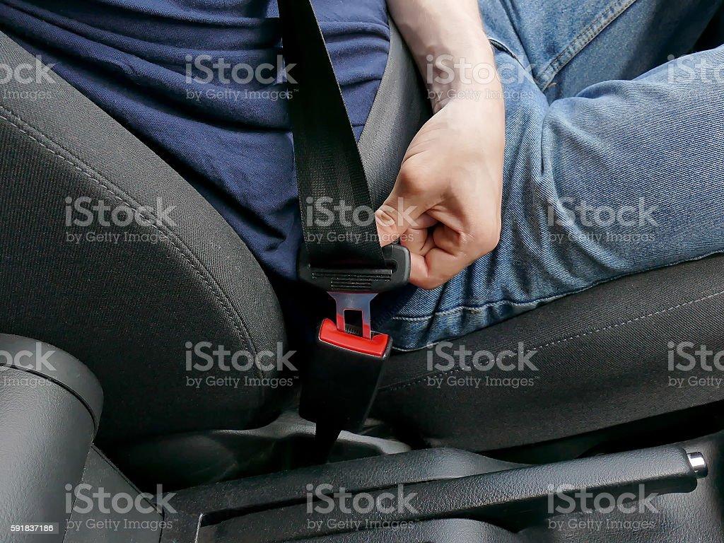 Details of hand putting on safety belt foto de stock libre de derechos