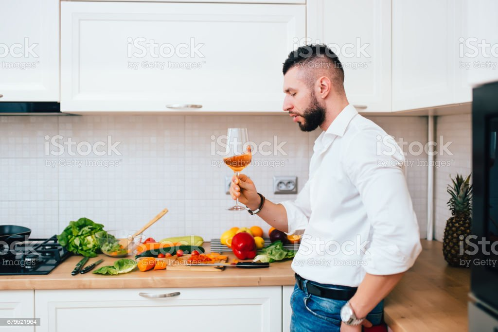 Details of perfect dinner. Confident male sommelier looking at wine glass standing in modern kitchen and cooking salad royalty-free stock photo