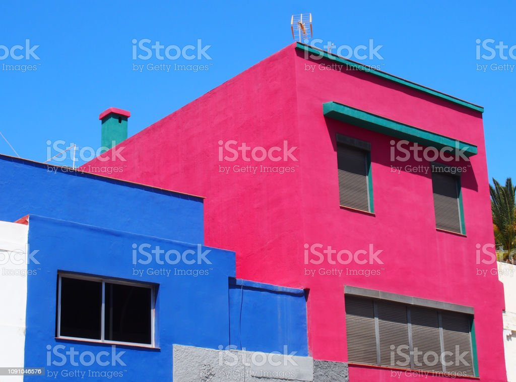 details of small angular pink and blue modern brightly painted concrete houses in spain stock photo