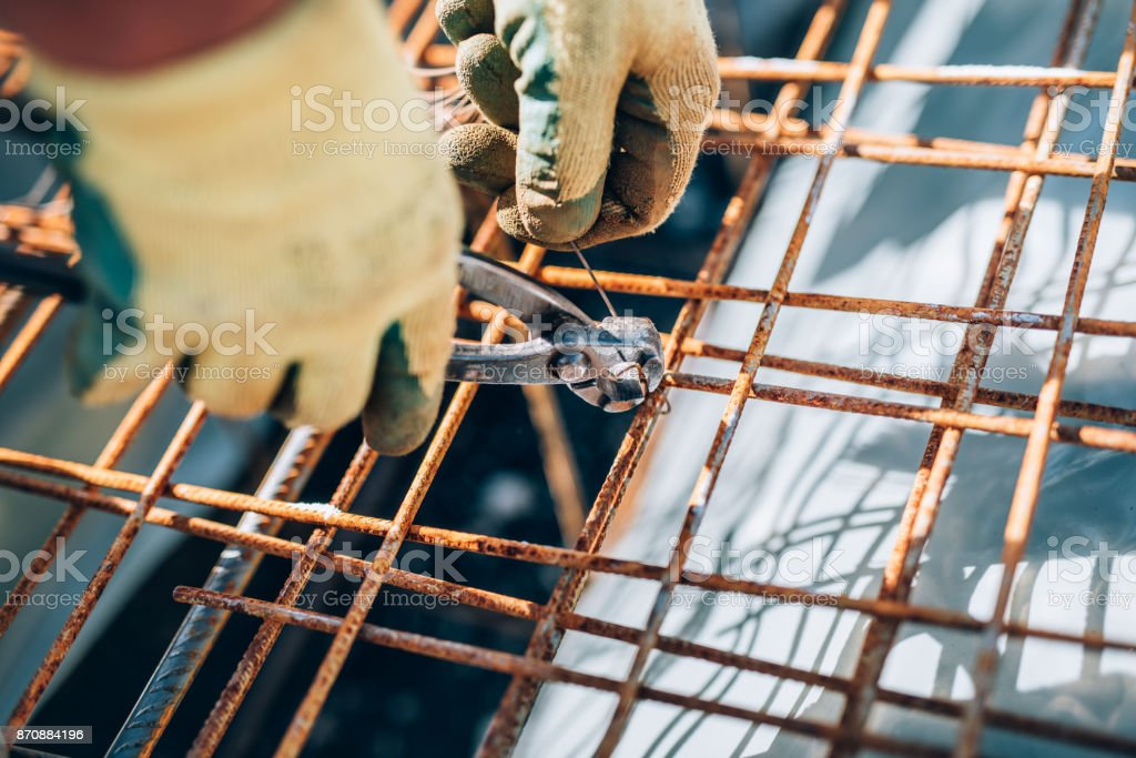 Details of steel reinforcement on construction site. Industrial construction worker using pliers and wire rod stock photo