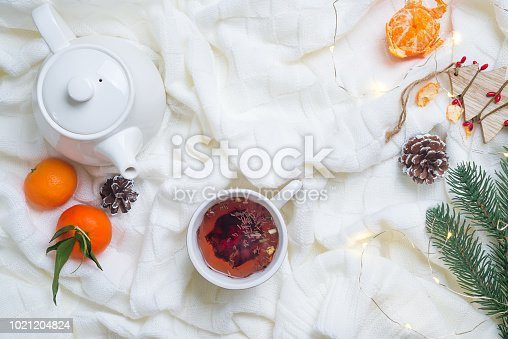 859424970istockphoto Details of still life in the home interior living room. Beautiful Cup of tea with tangerines on knitted white warm blanket . Cosy autumn-winter concept with copy space 1021204824