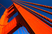 The orange anchor of the Golden Gate rises into the blue sky