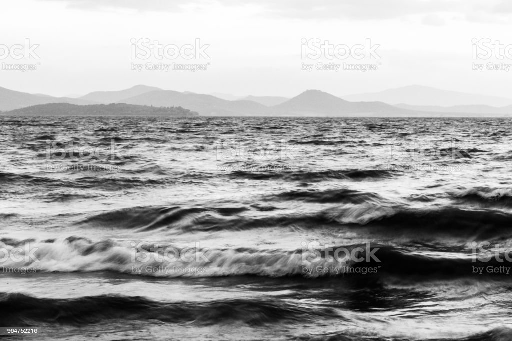 Details of waves in a lake, with distant hills in the background royalty-free stock photo