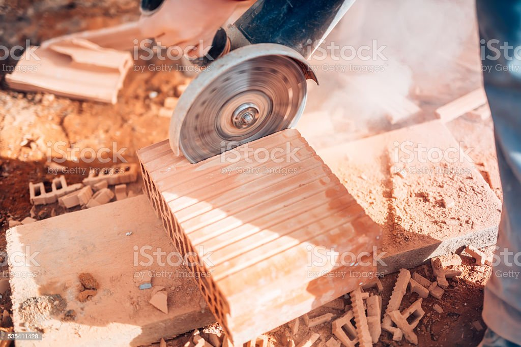 details of worker using angle grinder for cutting bricks stock photo