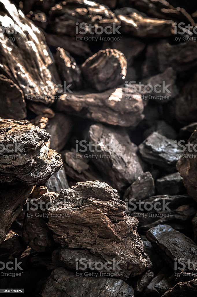 Details patterned surface texture ofpile of black  fossile wood, coal stock photo