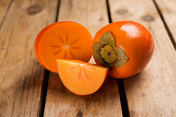 details persimmon fruit on rough wooden table - 柿 ストックフォトと画像