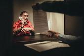 One male detective interrogating a prisoner in prison visiting room.