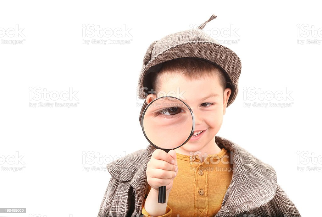 Detective boy is looking through magnifying glass stock photo