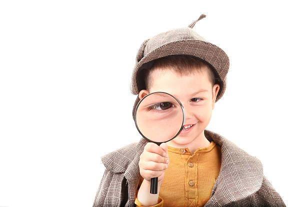 detective boy is looking through magnifying glass - sherlock holmes stock photos and pictures