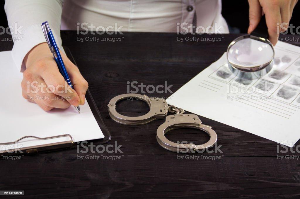 Detective expert writes data into the fingerprint table stock photo