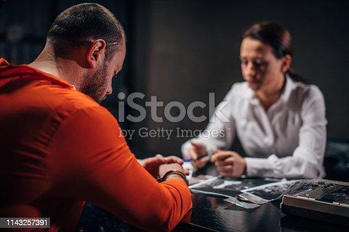 Woman detective investigating a man prisoner in dark investigation room.