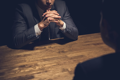 Detective interviewing suspect in dark room - investigation and interrogation concepts