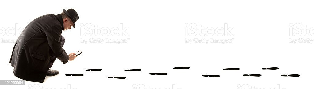 Detective investigate with magnifying glass is following tracks stock photo