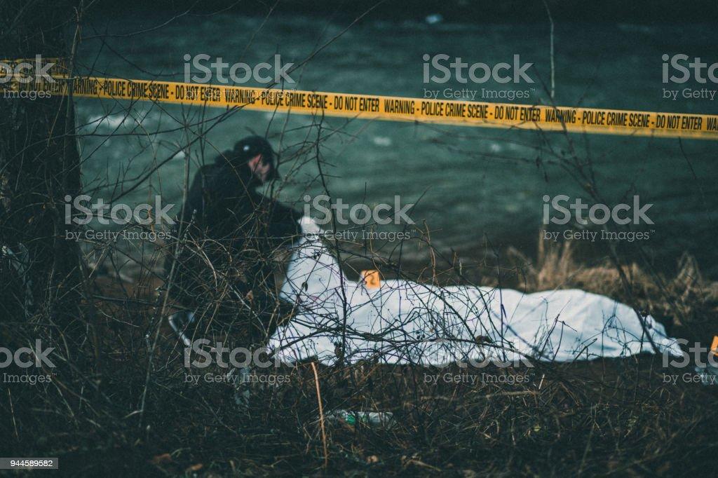 Detective investigating crime scene by the river stock photo