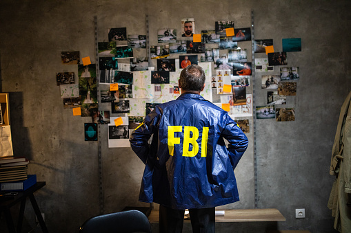 Rear view of FBI detective wearing FBI raincoat and looking at wall full of evidences and crime scene pictures with hands on hip