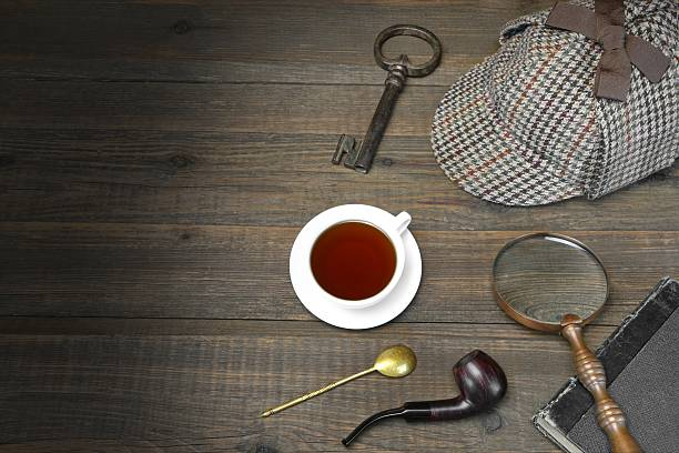 Detective or Investigator Concept. Private Detective Tools On Wooden Table Sherlock Holmes Concept. Private Detective Tools On The Wood Table Background. Deerstalker Cap,  Magnifier, Key, Cup, Notebook, Smoking Pipe. sherlock holmes stock pictures, royalty-free photos & images