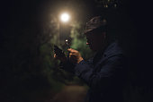 Detective agent with a gun in his hand is watching through a magnifying glass and searching for a clue.