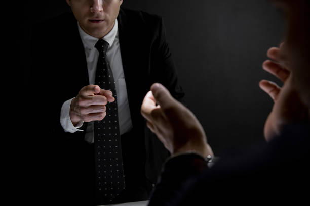 Detective pointing hand to criminal man in dark interrogation room Detective pointing hand to suspect or criminal man in dark interrogation room shock tactics stock pictures, royalty-free photos & images