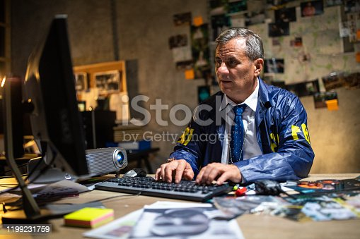 Mature FBI detective wearing shirt and tie, raincoat, using computer late at night at office. Map, crime scene pictures and adhesive notes on wall at background