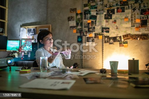 Female FBI detectives using projector in the office, watching something on projector, late at night while drinking coffee and smoking cigarette