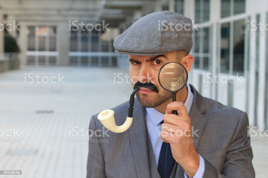 Detective with hat, pipe and magnifying glass stock photo