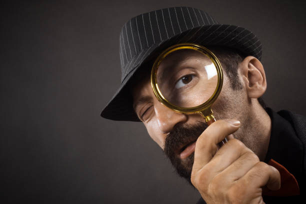 detective with loupe The old-fashioned detective with hat is looking through loupe or magnifier on dark gray background. detective stock pictures, royalty-free photos & images