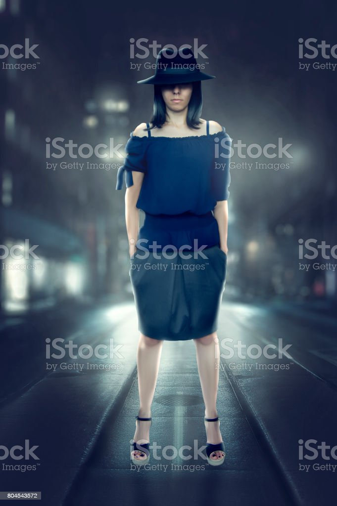Detective woman stops in a street at night and looks in camera with hat hiding eyes with fog stock photo