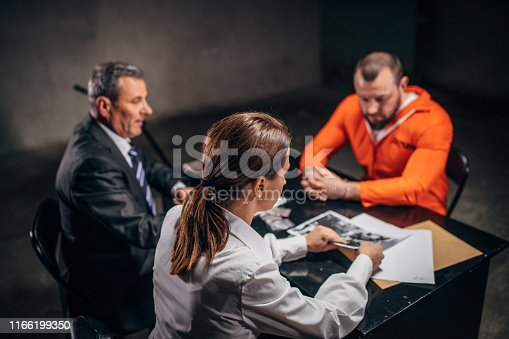 Three people, man and woman detectives interrogating a man prisoner in dark investigation room.