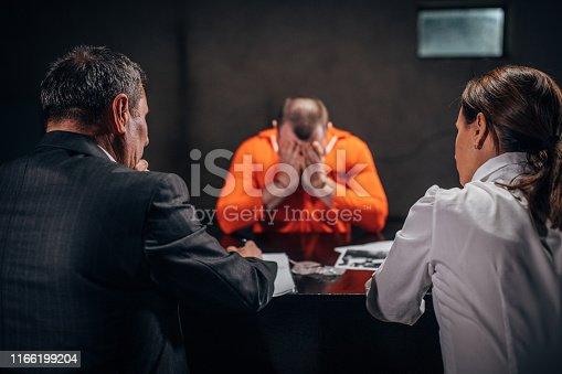 Three people, man and woman detectives interrogating a man prisoner in dark investigation room.