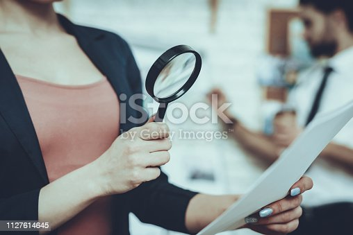 Detectives is Working in Private Detective Agency. Detectives is Young Caucasian Man and Woman. Woman is Looking on Paper with Magnifying Glass. Man is Standing at Clues Map on Background.