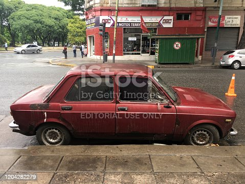Buenos Aires, Argentina - February 5, 2020: Red vintage Fiat car parked in the street in very bad condition. It is not unusual for people to leave the cars like this until they figure out what to do with them