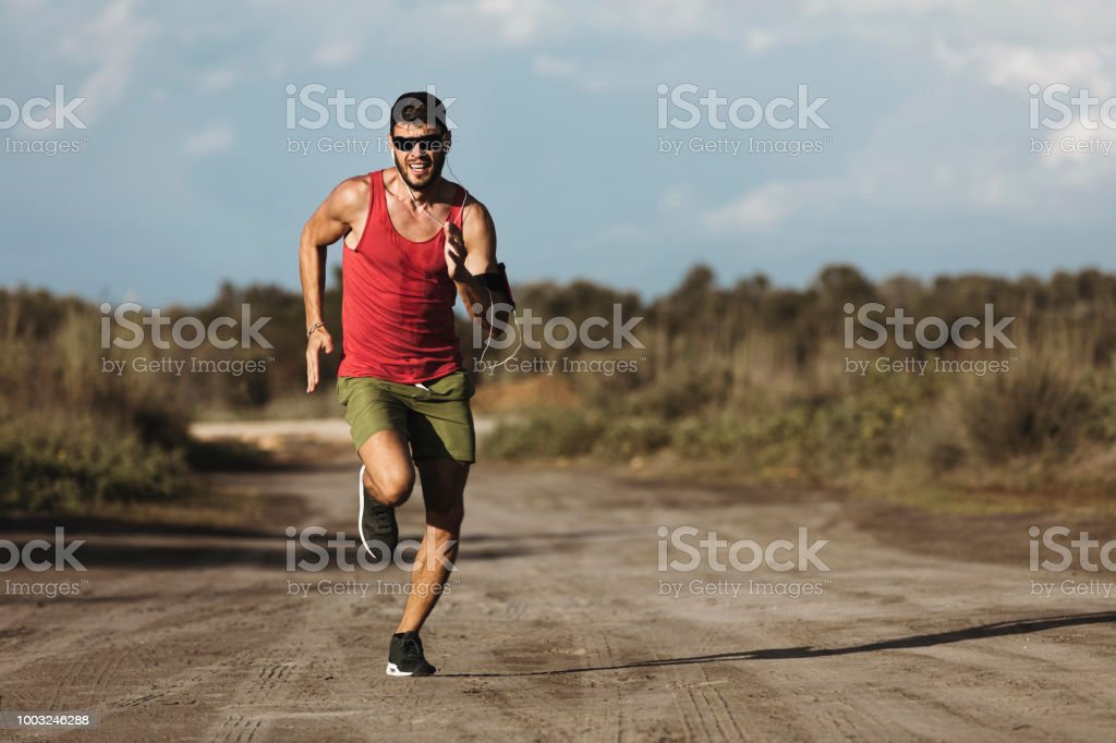 Young male runner out in the nature at summer sprinting
