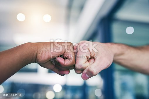 Cropped shot of two people giving each other a fist bump in a modern office
