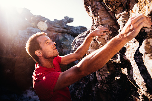 Determination in rock climbing man's face during ascent of mountain