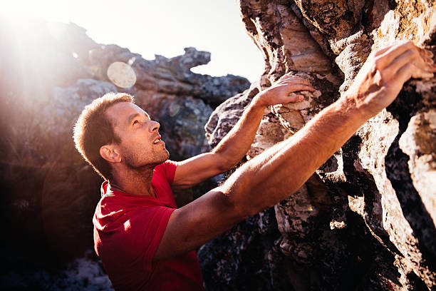 determination in rock climbing man's face during ascent of mountain - clambering stock photos and pictures
