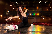 Beautiful brunette dancer, dressed in black, training on the stage for her dance, and doing side splits.