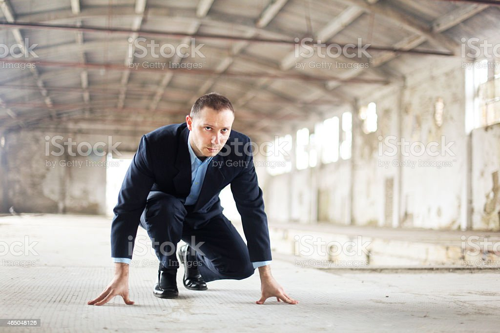Businessman in starting line position in a factory building