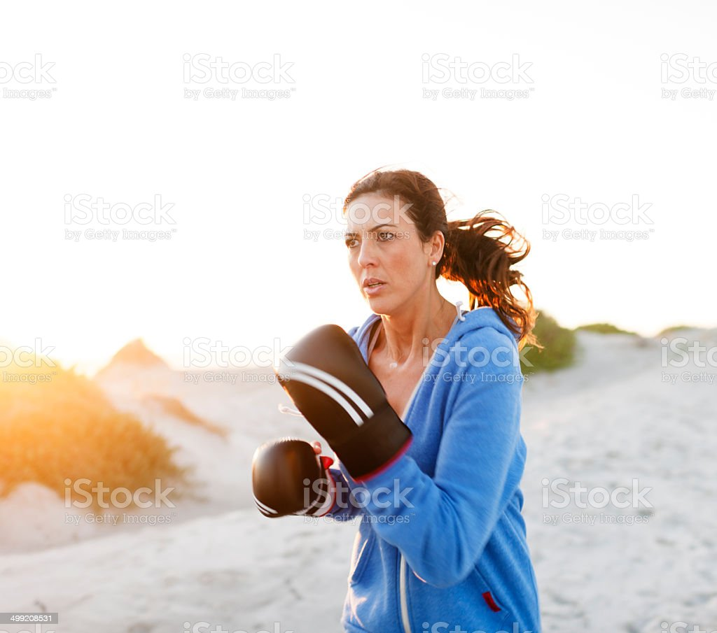Woman boxer running on the beach during a training session.