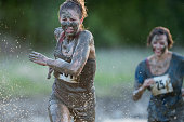 Beautiful young woman with blonde hair covered in mud running through splashing water wearing a race bib and muddy casual clothing during a mud run outdoors in the summer.