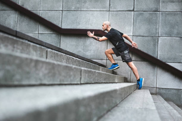 Determination Focussed runner man jogging on stairs agility stock pictures, royalty-free photos & images