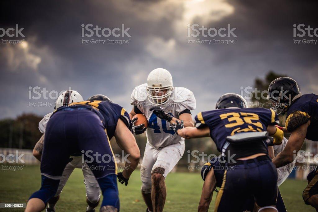 US-amerikanischer Footballspieler bemüht sich beim Durchgang durch Abwehrspielern bestimmt. – Foto