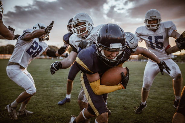 Determined American football player passing defensive players on a match. Young American football player making an effort while passing through defensive players with a ball. wide receiver athlete stock pictures, royalty-free photos & images