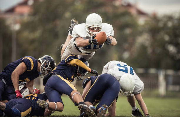 Determined American football player with a ball trying to score touchdown. Large group of tough American football players in action during the game on playing field. american football uniform stock pictures, royalty-free photos & images