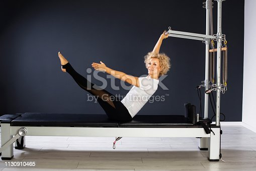 Portrait of beautiful best aged woman performing stretching exercise on reformer