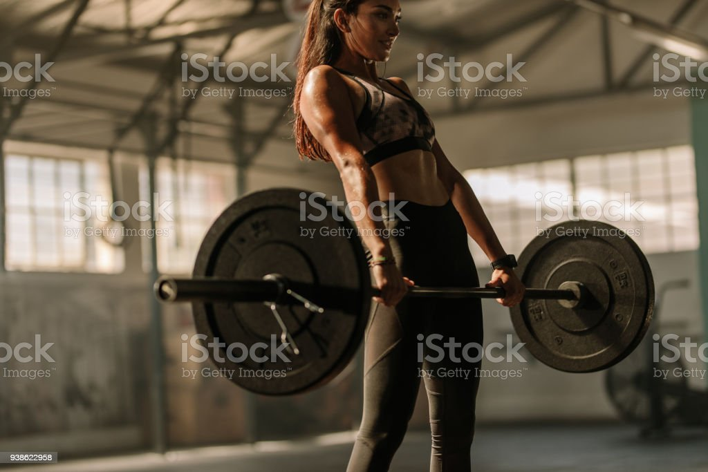 Determined and strong woman with heavy weights stock photo