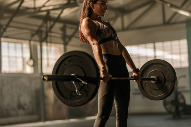determined and strong woman with heavy weights - pesistica foto e immagini stock