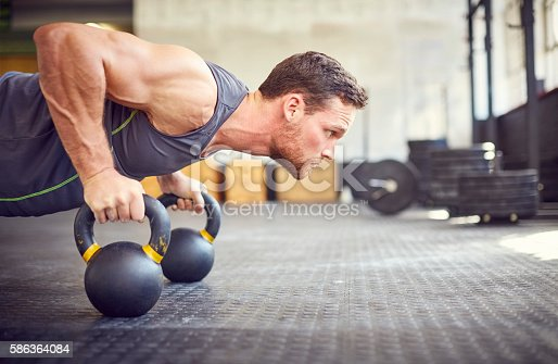 Determined athlete doing push-ups on kettlebells. Side view of man exercising in gym. Male is in health club.