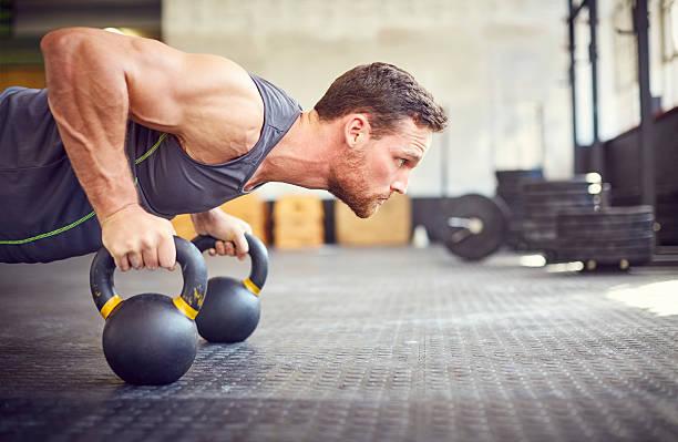 determined athlete doing push-ups on kettlebells in gym - pesa rusa fotografías e imágenes de stock