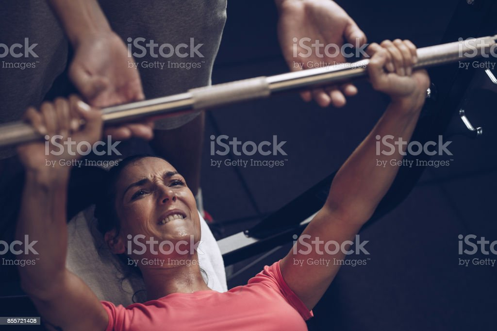 Determined athlete making an effort while doing bench press exercises with her coach. stock photo